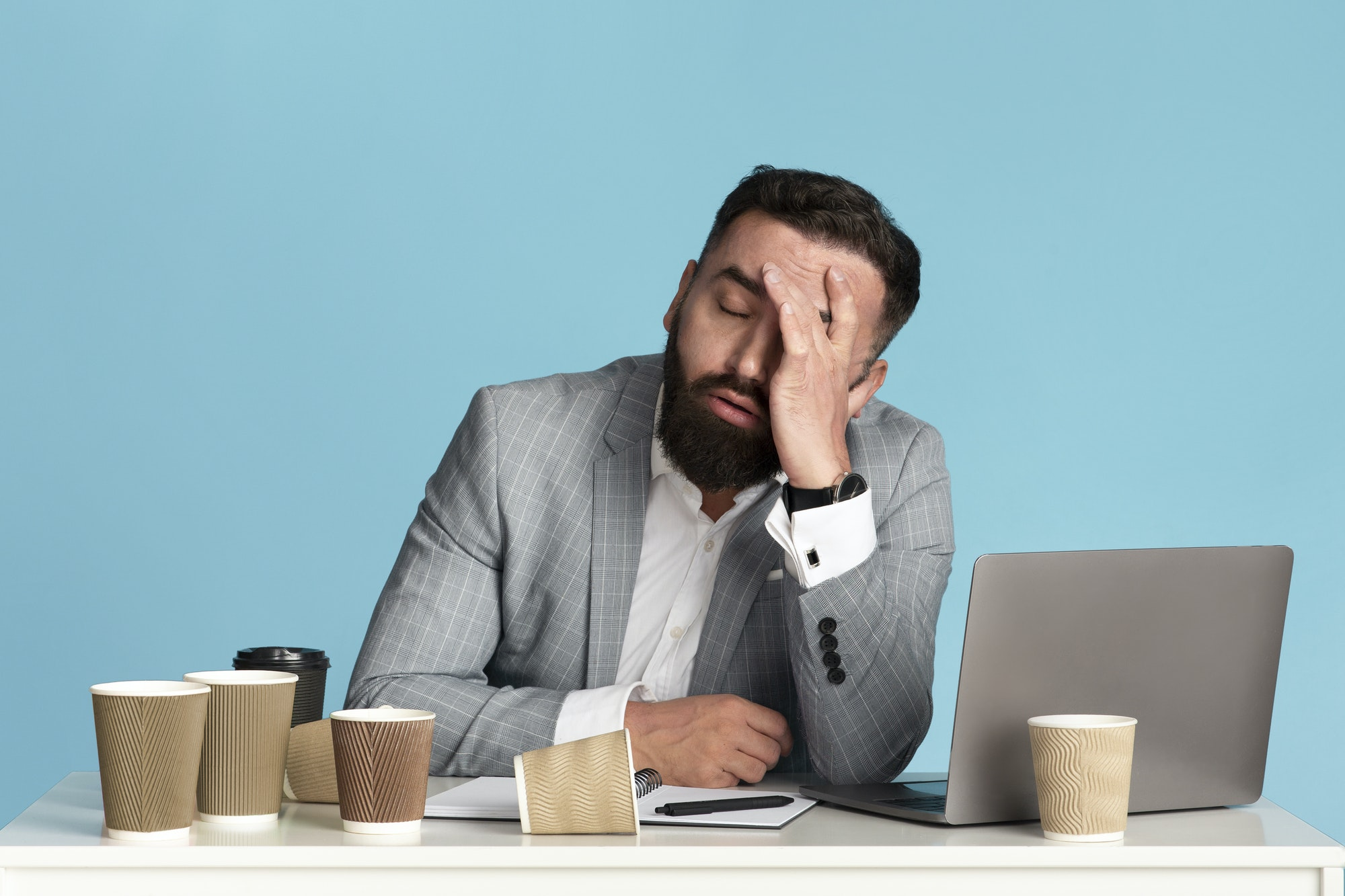 Working overtime. Exhausted businessman sitting at desk with laptop and empty coffee cups against
